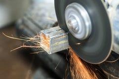 Máquina que enarena muchas chispas queman y trabajan corta un tubo cuadrado tenga tono Primer imágenes de archivo libres de regalías