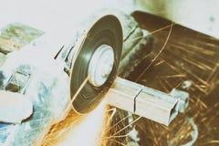 Máquina que enarena muchas chispas queman y trabajan corta un tubo cuadrado tenga tono Primer fotografía de archivo