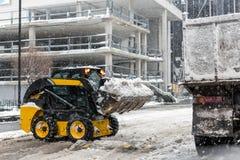 A máquina remove a neve de uma rua da cidade fotos de stock royalty free