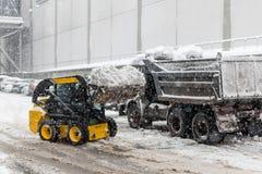 A máquina remove a neve de uma rua da cidade fotografia de stock royalty free