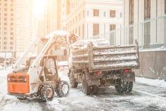 A máquina remove a neve de uma rua da cidade fotos de stock