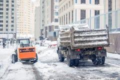 A máquina remove a neve de uma rua da cidade imagem de stock