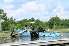 Máquina segador de la vegetación del lago en orilla Imágenes de archivo libres de regalías
