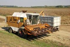 Máquina segador en el campo de maíz Imagenes de archivo