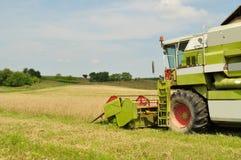 Máquina segadora en el campo de trigo durante la cosecha Fotos de archivo
