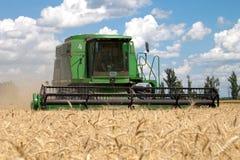 Máquina segadora que trabaja en un campo de trigo Foto de archivo libre de regalías