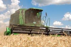 Máquina segadora que trabaja en un campo de trigo Fotografía de archivo
