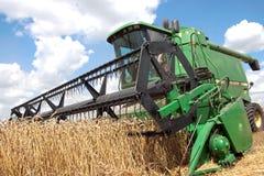 Máquina segadora que trabaja en un campo de trigo Imagen de archivo