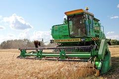 Máquina segadora que trabaja en un campo de trigo Imagenes de archivo