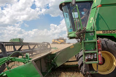 Máquina segadora que trabaja en un campo de trigo Foto de archivo
