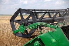 Máquina segadora que trabaja en un campo de trigo Imagen de archivo libre de regalías