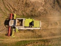 Máquina segadora - vista aérea de la máquina segadora moderna en la cosecha del trigo en el campo de trigo de oro en el verano Fotografía de archivo
