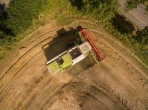 Máquina segadora - vista aérea de la máquina segadora moderna en la cosecha del trigo en el campo de trigo de oro en el verano Fotos de archivo