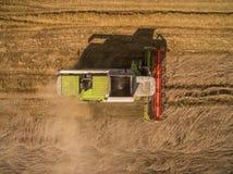 Máquina segadora - vista aérea de la máquina segadora moderna en la cosecha del trigo en el campo de trigo de oro en el verano Imagen de archivo