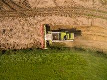 Máquina segadora - vista aérea de la máquina segadora moderna en la cosecha del trigo en el campo de trigo de oro en el verano Imágenes de archivo libres de regalías