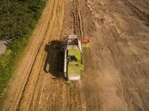 Máquina segadora - vista aérea de la máquina segadora moderna en la cosecha del trigo en el campo de trigo de oro en el verano Imagen de archivo libre de regalías