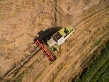 Máquina segadora - vista aérea de la máquina segadora moderna en la cosecha del trigo en el campo de trigo de oro en el verano Fotografía de archivo libre de regalías