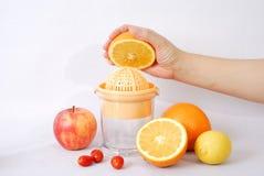 Máquina y mano del zumo de fruta Imágenes de archivo libres de regalías