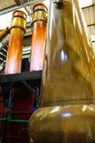 Máquinas de cobre enormes de la destilación en el oro y la naranja brillantes Colo imagen de archivo libre de regalías