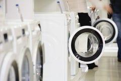 Máquinas de lavar na loja de dispositivo e em comprador defocused Imagem de Stock