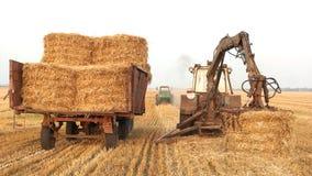 Máquinas de los tractores para cosechar alrededor de las balas de heno imágenes de archivo libres de regalías