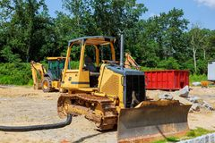 máquinas escavadoras do trator da construção nova e recipientes do lixo Fotografia de Stock Royalty Free