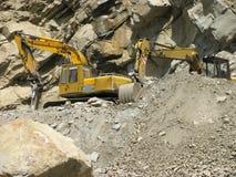 Máquinas industriales que cavan en la montaña Foto de archivo libre de regalías