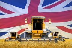 4 m?quinas segadoras anaranjadas en campo de trigo con el fondo de la bandera, concepto BRIT?NICO de la agricultura de Reino Unid imágenes de archivo libres de regalías