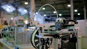 Máquinas tridimensionales automáticas 3D en la fila que trabaja en la exposición de la tecnología metrajes