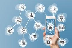 Márketing móvil en línea leveraging datos grandes, analytics y medios sociales Concepto con la mano que sostiene el teléfono eleg