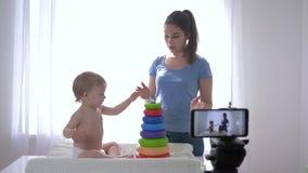 Márketing moderno, feliz muchacho del niño con el vlogger de la momia jugado por los juguetes educativos mientras que registra el almacen de video
