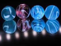 4 mármores de vidro coloridos com um fundo escuro Fotografia de Stock Royalty Free