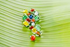 Mármores de vidro coloridos na folha da banana foto de stock