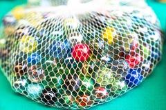 Mármores de vidro coloridos na rede fotos de stock