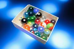 Mármores de vidro na caixa imagens de stock