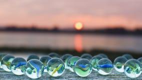 Mármores de vidro no por do sol imagens de stock royalty free