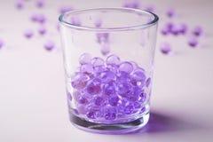 Mármores roxos em beber o vidro transparente com mármores dispersados no fundo branco fotos de stock