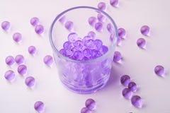 Mármores roxos em beber o vidro transparente com mármores dispersados no fundo branco foto de stock