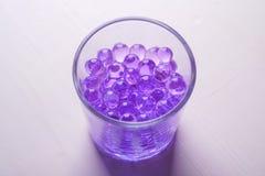 Mármores roxos em beber o vidro transparente no fundo branco imagens de stock royalty free
