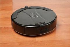más aspirador robótico negro corre en el piso laminado El robot es controlado por los controles por voz para la limpieza directa  foto de archivo