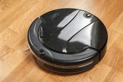 más aspirador robótico negro corre en el primer laminado del piso El robot es controlado por los controles por voz para la limpie foto de archivo libre de regalías