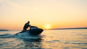 Más jetskier profesional está cruzando las aguas abiertas en la puesta del sol almacen de video