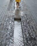 Más Londres en la orilla sur del río Támesis La foto muestra las piernas del niño que juegan en el waterin un canal en la calle fotografía de archivo libre de regalías