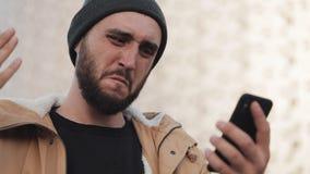 Más notícias da leitura do homem novo na posição do smartphone perto do centro do escritório olha shockes e preocupa ao verificar video estoque