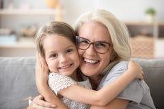 Más vieja abuela feliz que abraza a poca muchacha del nieto que mira a fotos de archivo libres de regalías
