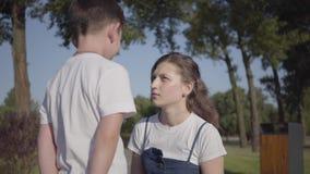Más vieja hermana estricta que regaña a su hermano menor en el parque del verano Relación entre los hermanos El caminar del mucha almacen de video
