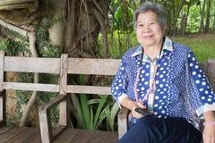 Más vieja mujer asiática que sostiene el teléfono elegante móvil mientras que se sienta en el ch Imágenes de archivo libres de regalías