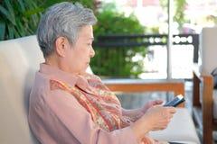 más vieja mujer asiática que sostiene el teléfono móvil en casa u mayor mayor fotos de archivo libres de regalías