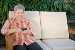 más vieja mujer asiática que sostiene el teléfono móvil en casa u mayor mayor fotografía de archivo libre de regalías