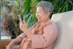 más vieja mujer asiática que sostiene el teléfono móvil en casa u mayor mayor fotografía de archivo